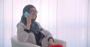 Closeup side view portrait of young muslim attractive female doctor in hijab and white coat having a phone call sitting. In the armchair stock footage