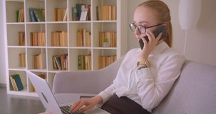 Closeup side view portrait of young pretty caucasian blonde businesswoman in glasses using the laptop and having a phone. Call sitting on the couch stock footage