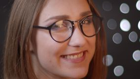 Closeup side view portrait of young pretty caucasian girl in glasses looking at camera and smiling seductively with stock footage