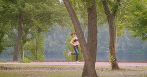 Closeup side view portrait of young pretty sporty female runner jogging in the park in urban city outdoors.  stock video