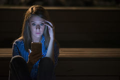 Closeup side view portrait of young sad thoughtful woman leaning  against street lamp at night Royalty Free Stock Photos