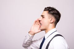 Closeup side view profile portrait, angry upset young man, worker, employee, business man, hand to mouth, open mouth yelling, isol royalty free stock image
