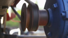 Red detail turns round and moves belt on equipment. Closeup side view red metal detail turns round and moves belt on modern geodetic equipment stock footage