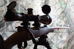 Rifle on Bipod. Closeup side view of a rifle on a bipod with camo background Royalty Free Stock Images