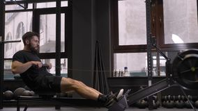 Closeup side view shoot of adult muscular athletic man using rowing machine indoors in the gym.  stock footage