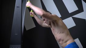 Closeup side view shoot of muscular shirtless athletic man training on the cable cross over in the gym.  stock video