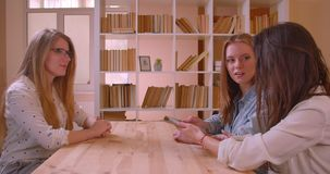 Closeup side view shoot of young beautiful lesbian couple talking to female realtor with the tablet about purchase of an. Apartment sitting by the table indoors stock video footage