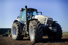 closeup side view tractor on big wheels on ploughed field Royalty Free Stock Image