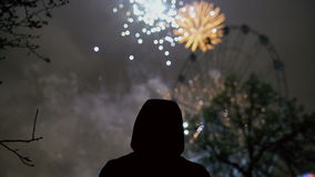 Closeup silhouette of alone man watching fireworks on new year celebration outdoors. Closeup silhouette of alone man watching fireworks on new year celebration stock footage