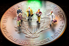 Investing in silver coins. Closeup of silver american eagle coin with a reflection of close digital device and miniature business men figurines having a meeting royalty free stock photography