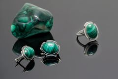 Closeup silver earrings and ring with malachite on background of malachite stone piece on black acrylic desk. Stock Images