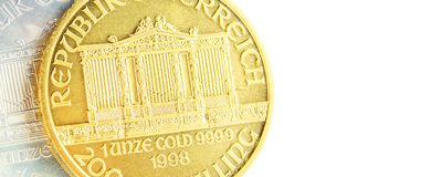 Silver and golden austrian philharmoniker one ounce coins. Closeup of silver and golden austrian philharmoniker one ounce coins on white background placed on stock images