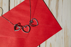 Closeup of silver heart pendants on a red envelope Royalty Free Stock Images
