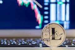 Silver litecoin stay on background of chart. Closeup of silver litecoin stay on background from chart on the monitor Royalty Free Stock Photo