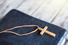 Closeup of simple wooden Christian cross necklace. On holy Bible Stock Photos