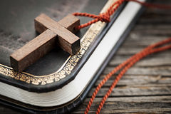 Cross on Bible. Closeup of simple wooden Christian cross necklace on holy Bible Royalty Free Stock Images