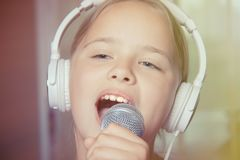 Closeup of singing caucasian child girl. Young girl emotionally sings into the microphone, holding it with hand. Closeup of singing caucasian child girl. Young stock image