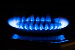 Blue flame of low caloric methane gas. Closeup of a single blue gas flame in front of a black background royalty free stock image