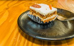 Closeup of single piece of carrot cake decorated with a pecan. And candy carrot on black plate sitting on a wooden table top stock photography