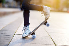 Closeup of skateboarder legs. Kid riding skateboard outdoor. Royalty Free Stock Images