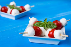 Closeup of skewers with mozzarella, cherry tomatoes and basil stock images