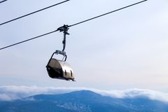 Closeup ski lift on the cable car with a closed cabin on the bac royalty free stock images