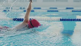 Closeup. Skillful female swimmer trains in the pool. She crawling or crawlstroke and makes a stroke with her hands. She. Wear swim cap and protective goggles stock video