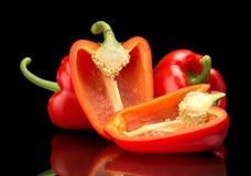 Closeup skivade röda spanska peppar som isoleras på svart Arkivfoton