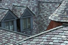 Closeup of slate tiled roofs in shades of grey and green stock images