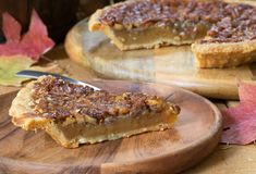 Slice of Pecan Pie. Closeup of a slice of pecan pie with autumn leaves Stock Photos