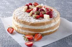 Amazingly delicious sponge cake and whole, slices of strawberries on the baking paper, gray surface royalty free stock images