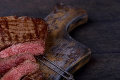 Closeup sliced medium rare steak on cutting board. And wooden background royalty free stock photo