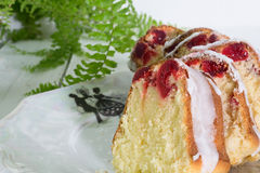 Closeup of slices of glazed cherry cake on vintage plate with bo Stock Photography