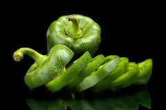 Closeup slices of green bell peppers on black with drops of wate Stock Image
