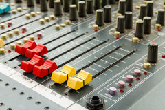 Closeup on sliders of sound mixing console in audio recording. Closeup on red and yellow sliders of sound mixing console in audio recording studio Royalty Free Stock Images