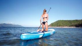 Close blonde girl in bikini paddles board to green coast stock footage