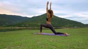 Closeup Slim Girl Stands Yoga Pose on Purple Karimat. Closeup slim blond girl stands in yoga pose Virabhadrasana on purple karimat on green grass near lake stock video