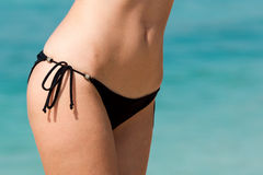 Closeup of slim woman belly in bikini on beach. Closeup of slim woman belly in black bikini on water background Royalty Free Stock Images