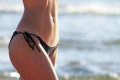 Closeup of slim woman belly in black bikini Stock Photos