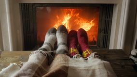 Closeup slow motion video of couple in love in warm socks lying under blanket at living room with burning fireplace