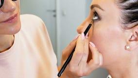 Closeup slow motion footage of professional visagiste painting models eyes. Maeup artist applying makeup on girls face stock video
