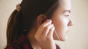 Closeup slow motion footage of upset teenage girl putting earphones in her ears. Slow motion footage of upset teenage girl putting earphones in her ears stock video footage