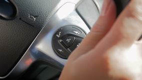Closeup slow motion footage of driver holding hands on steering wheel while driving car. Closeup slow motion video of driver holding hands on steering wheel stock footage