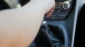 Closeup slow motion footage of driver shifting manual gearbox stick while driving car. Closeup slow motion video of driver shifting manual gearbox stick while stock video