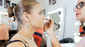 Closeup slow motion footage of professional makeup artist applying makeup on models face before fashion show stock video footage