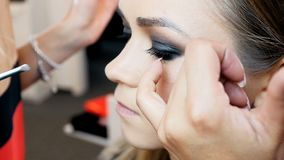 Closeup slow motion video of professional makeup artist painting eyes and applying mascara. Visagiste preparing model stock video footage