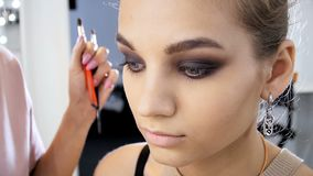 Closeup slow motion video of professional makeup artist painting eyes and applying mascara. Visagiste preparing model stock footage