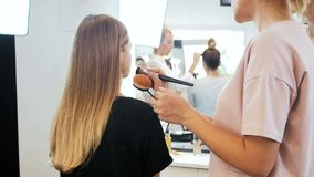 Closeup slow motion video of professional makeup artist working with model in visage studio. Woman applying cosmetics. Closeup slow motion footage of stock footage