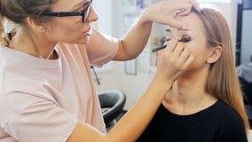 Closeup slow motion footage of professional visagiste painting models eyes. Maeup artist applying makeup on girls face. Closeup slow motion video of professional stock video footage
