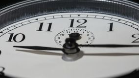 Closeup on slowly rotating clock face with fast moving clock hands stock video footage